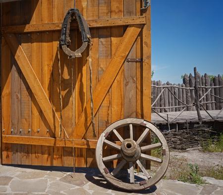 carreta madera: vieja rueda de carro de madera cerca de la puerta abierta