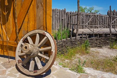 open gate: old wooden wagon wheel near the open gate
