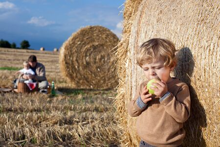 Adorable toddler eating apple on golden field photo