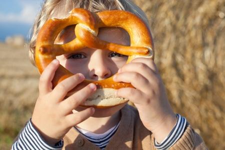 Little baby toddler with soft fresh German pretzel