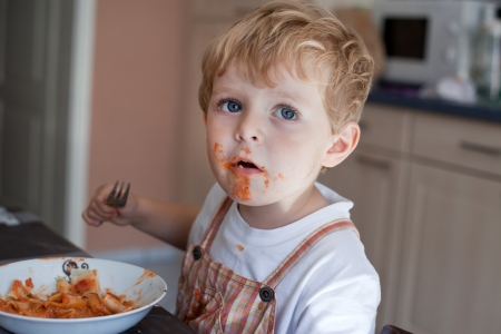 Adorable baby boy eating pasta with dirty face