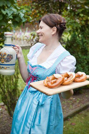 dirndl dress: Happy beautiful girl in dirndl dress holding Oktoberfest  pretzel in hands