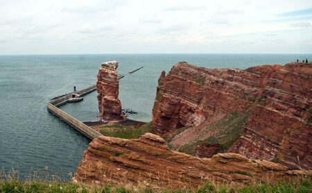 red bluff: Cliff line of Heligoland with the Tall Anna, the landmark of Heligoland on cloudy day Stock Photo