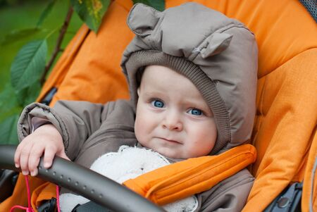 baby stroller: Sweet baby boy in winter clothes autumn day Stock Photo