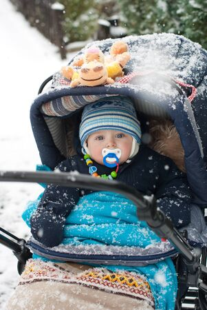 Baby boy sitting in pram during winter snow fall photo