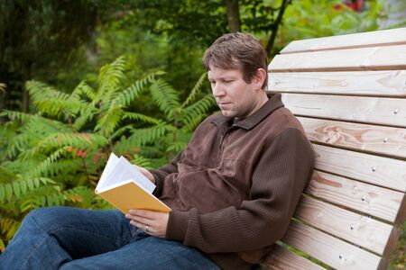 Young man reading book on wooden bench in autumn forest photo
