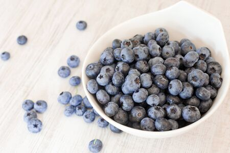 White bowl cup with fresh ripe blueberries  on wooden table Stock Photo - 15755572
