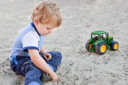 Little toddler boy playing with sand and toy on playground in summer photo