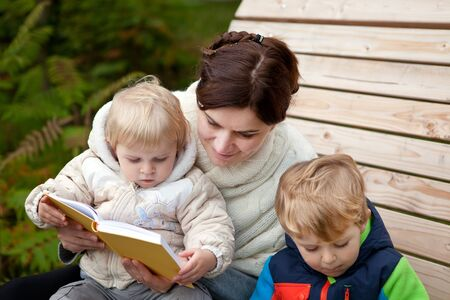 Young mother and toddler reading book in autumn park photo