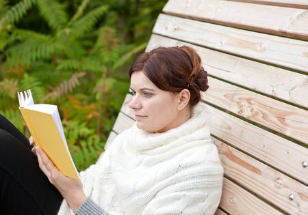Beautiful woman reading book on bench in autumn park photo