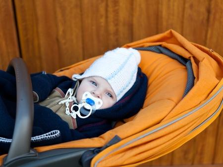 Lovely baby boy outdoor in orange stroller autumn photo