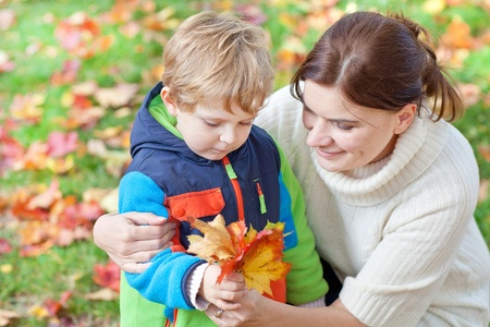 Little toddler boy and young mother in the autumn park playing with red and yellow leaves photo