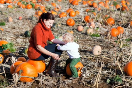 Little toddler boy and his mother in a field of pumpkins photo
