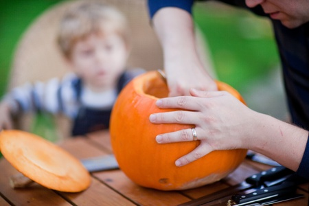 Young man and toddler boy making jack-o-lantern for halloween in autumn garden Stock Photo