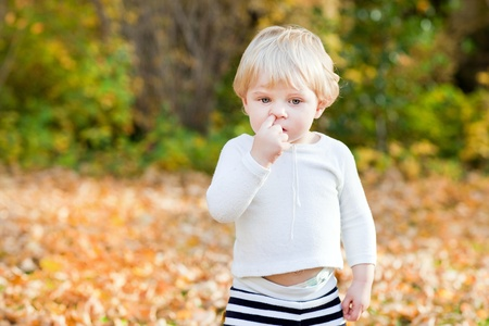 nose picking: Little toddler boy picking his nose in autumn park