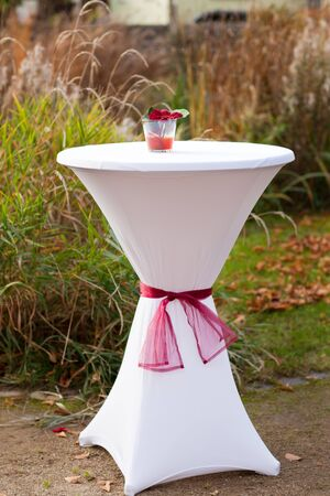 Bar table decorated with flowers for outdoor autumn wedding photo
