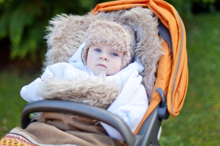 Little baby boy in warm winter clothes and orange pram outdoor photo