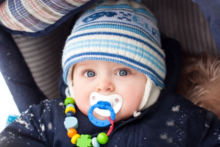 Little baby boy in pram during winter snow fall