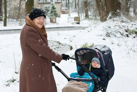 Great-grandmother walking with baby boy in pram during snowfall photo