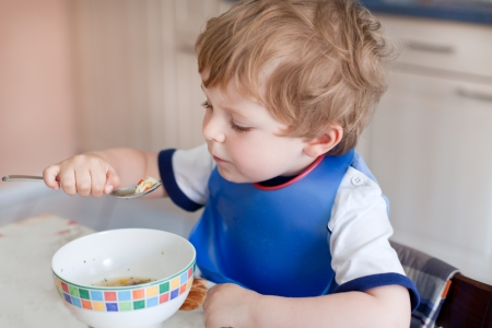 Adorable toddler boy eating healthy soup in the kitchen