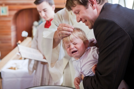 Little baby boy being baptized in catholic church holding by father photo