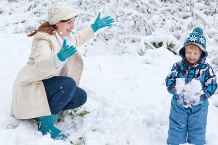 Young mother and little toddler boy having fun with snow outdoors on beautiful winter day photo