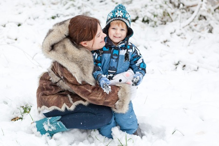 Young mother and little toddler boy having fun with snow outdoors on beautiful winter day Stock Photo - 16011006