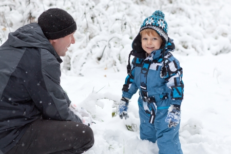 Young father and little toddler boy having fun with snow outdoors on beautiful winter day photo