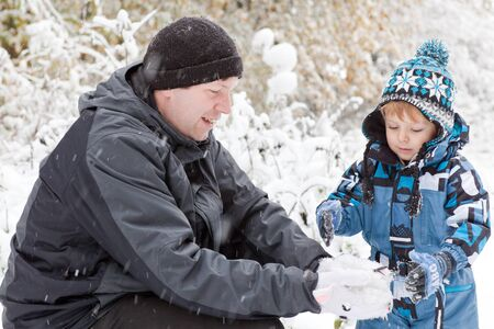 Young father and little toddler boy having fun with snow outdoors on beautiful winter day Stock Photo - 16010986