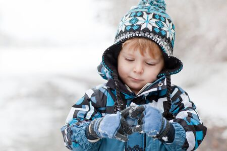 Little toddler boy having fun with snow outdoors on beautiful winter day Stock Photo - 16011008