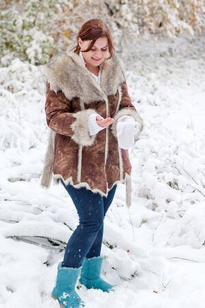 Young beautiful woman having fun with snow outdoors on beautiful winter day Stock Photo - 16010985