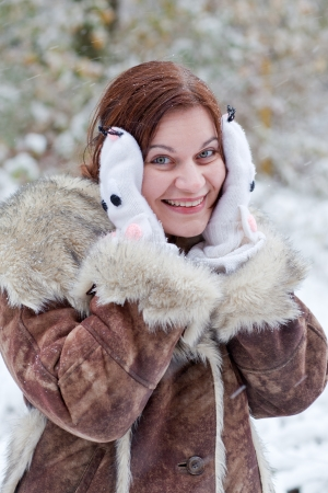 Young beautiful woman having fun with snow outdoors on beautiful winter day photo