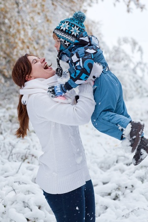 Young mother and little toddler boy having fun with snow outdoors on beautiful winter day Stock Photo - 16010977
