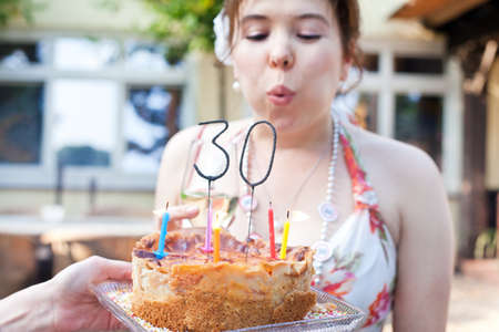 Young beautiful woman blowing out birthday candles 30 with focus on candle photo