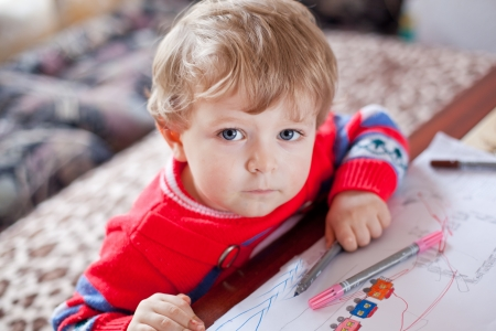Little toddler boy with blue eyes drawing indoor with colorful pens photo