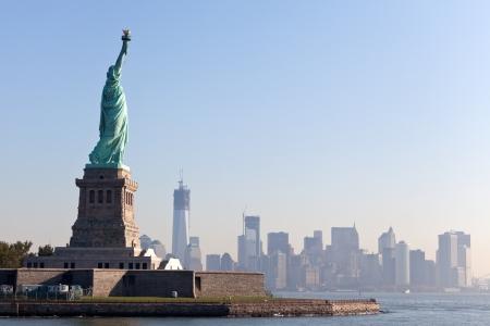 nowy: Statue of Liberty darmo turystów i Nowym Jorku w centrum miasta wczesnym rankiem na słonecznym Zdjęcie Seryjne