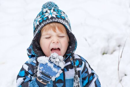 Little toddler boy having fun with snow outdoors on beautiful winter day photo