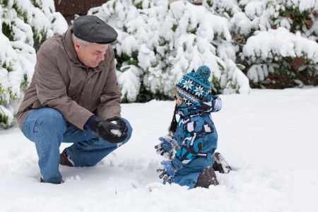 Grandfather and little toddler boy having fun with snow outdoors on beautiful winter day photo