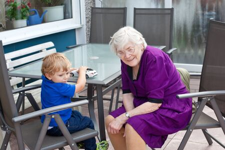 Grandmother and toddler boy  on patio on summer day photo