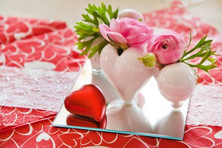 Vase with flowers and table setting in red decorated for romantic Valentins Day dinner photo