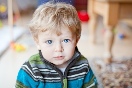 Beautiful toddler boy with blue eyes and blond hairs indoor photo