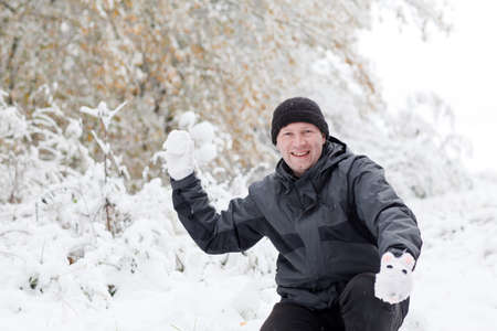 Young man having fun with snow outdoors on beautiful winter day photo