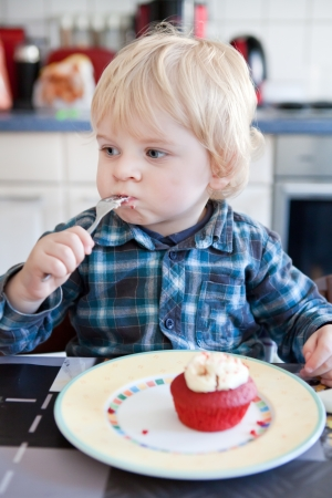Little toddler boy eating red velvet cupcake in home kitchen Stock Photo