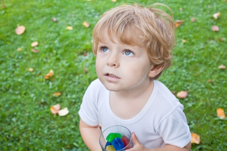Beautiful toddler boy in summer garden with glass of colorful ice cubes photo