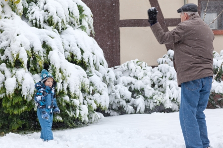 Grandfather and little toddler boy having fun with snow outdoors on beautiful winter day Stock Photo - 16405728