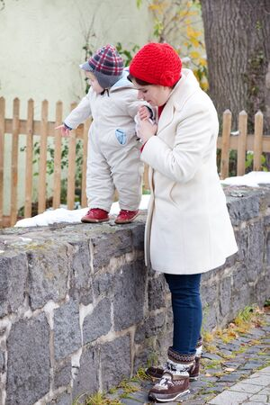 Young mother and little toddler boy walking outdoors on beautiful winter day photo