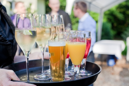 Waiter with dish of champagne, coctails, beer and juice glasses Stock Photo