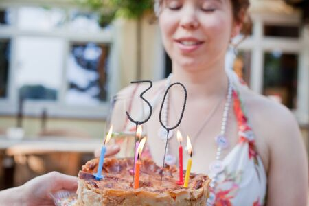 Young beautiful woman blowing out birthday candles 30 with focus on 30 and cake photo