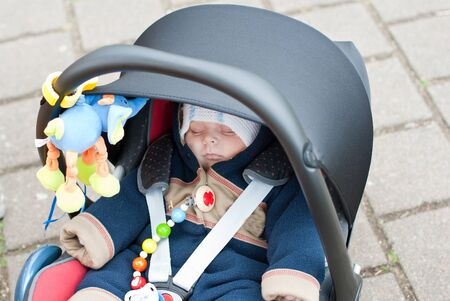Adorable baby boy in winter clothes sleeping in child car seat photo