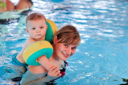 Little baby with blue eyes learning to swim with mother Stock Photo